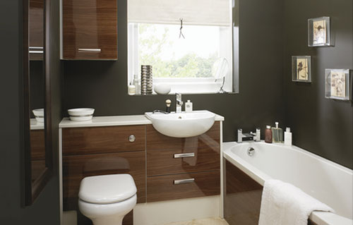 A glossy brown bathroom with pictures on the wall.
