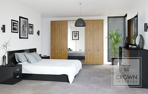 A large bedroom from Crown Imperials lifespace range featuring Crowns Furore black gloss furniture and Olive Light wood effect fronted wardrobe.
