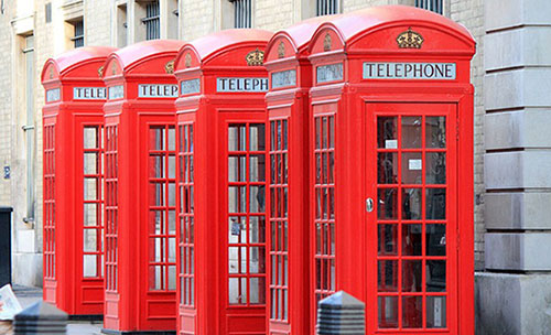 Five red telephone boxes next to each other backing onto a building.