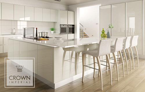 A modern white gloss kitchen from Crown Imperials Calypso range with a wooden floor.